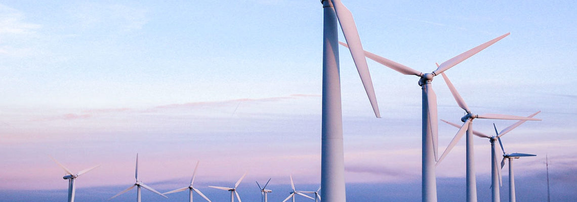 white wind turbines in a field with a blue pink sky